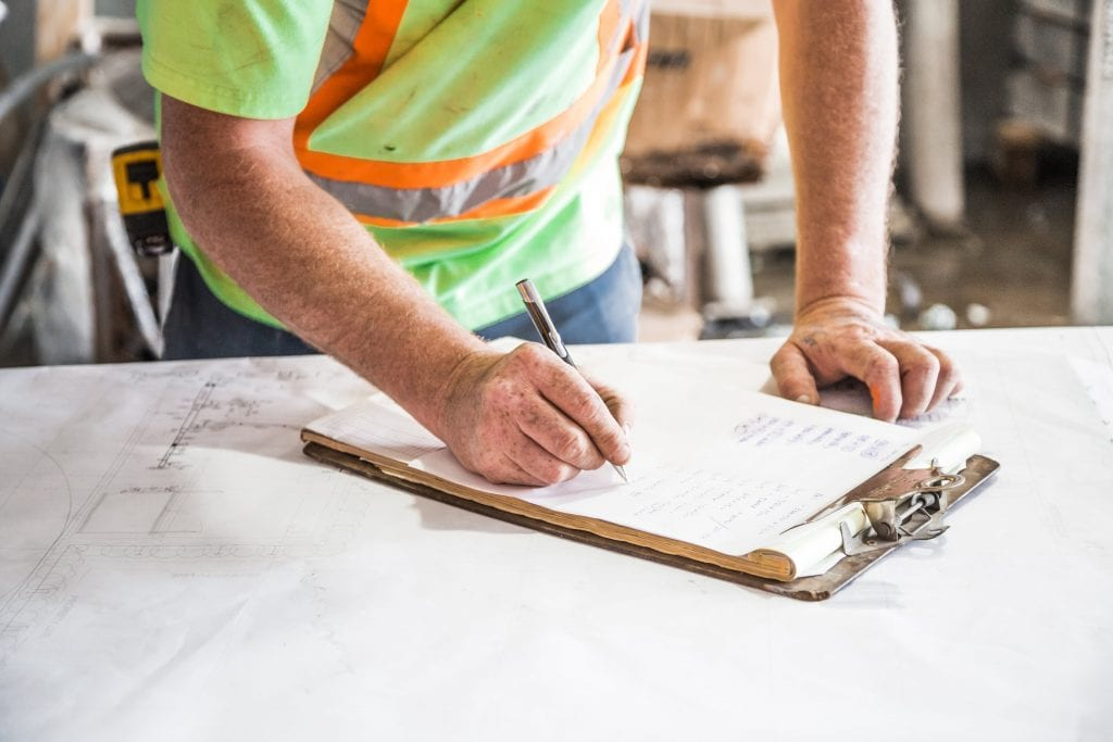 Image of a contractor in a yellow and orange hi-vis top, writing on paper attached to a clipboard.