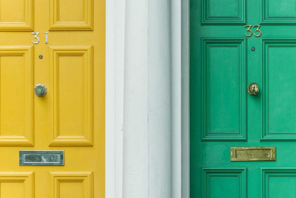 Image of a pair of wooden doors, one painted in yellow and the other in green.