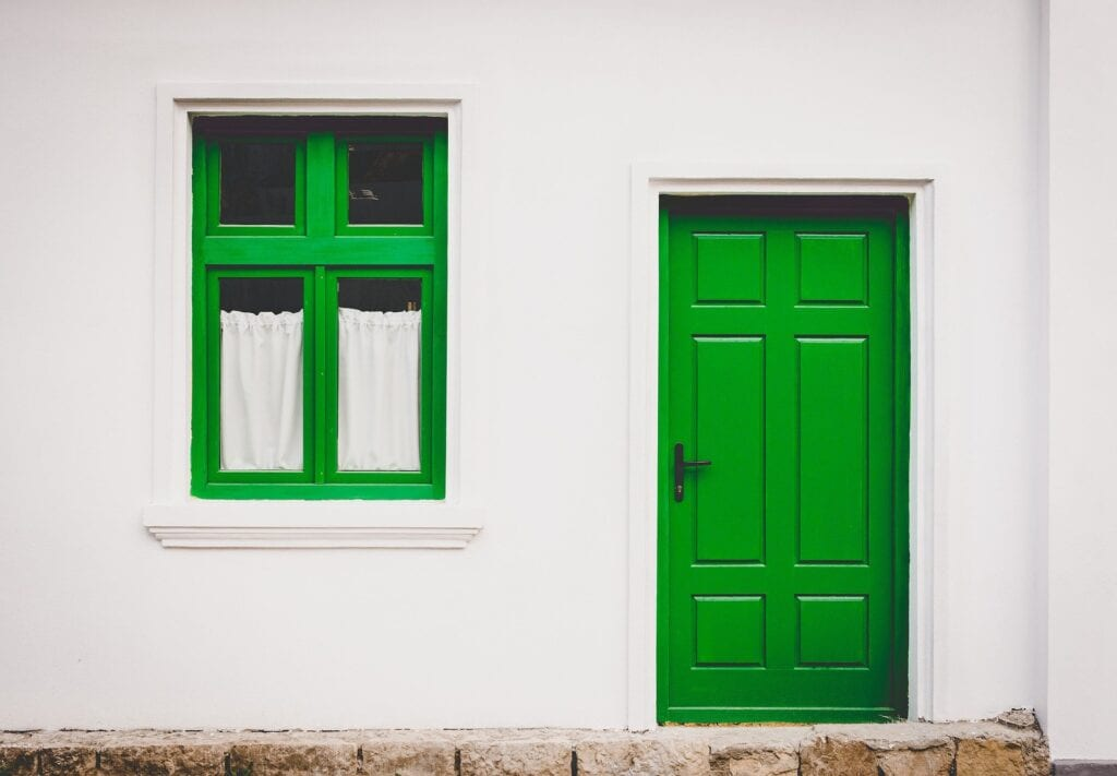 Window Colours: Image of a white house with a green window and door.