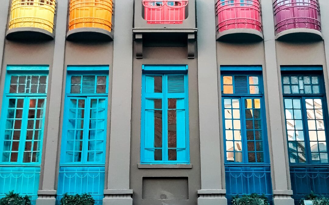 Window Colours: Image of a grey building with various rainbow coloured large windows.