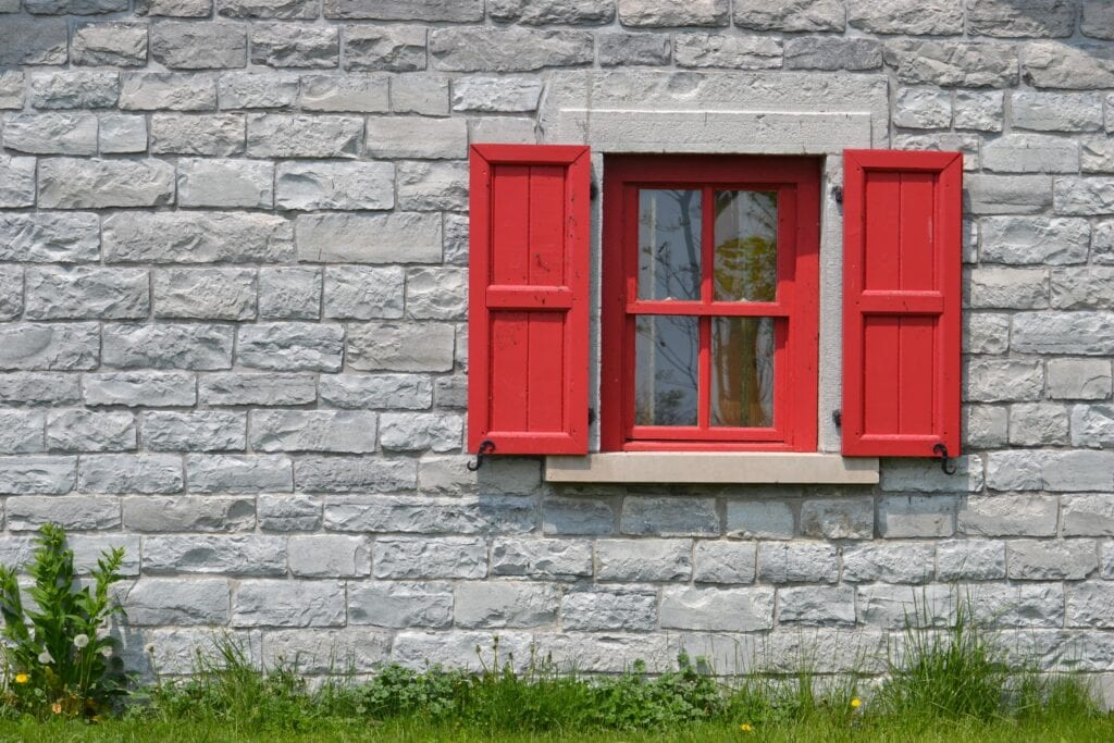 Window Colours: Image of a grey stone cottage with a red window and shutters.