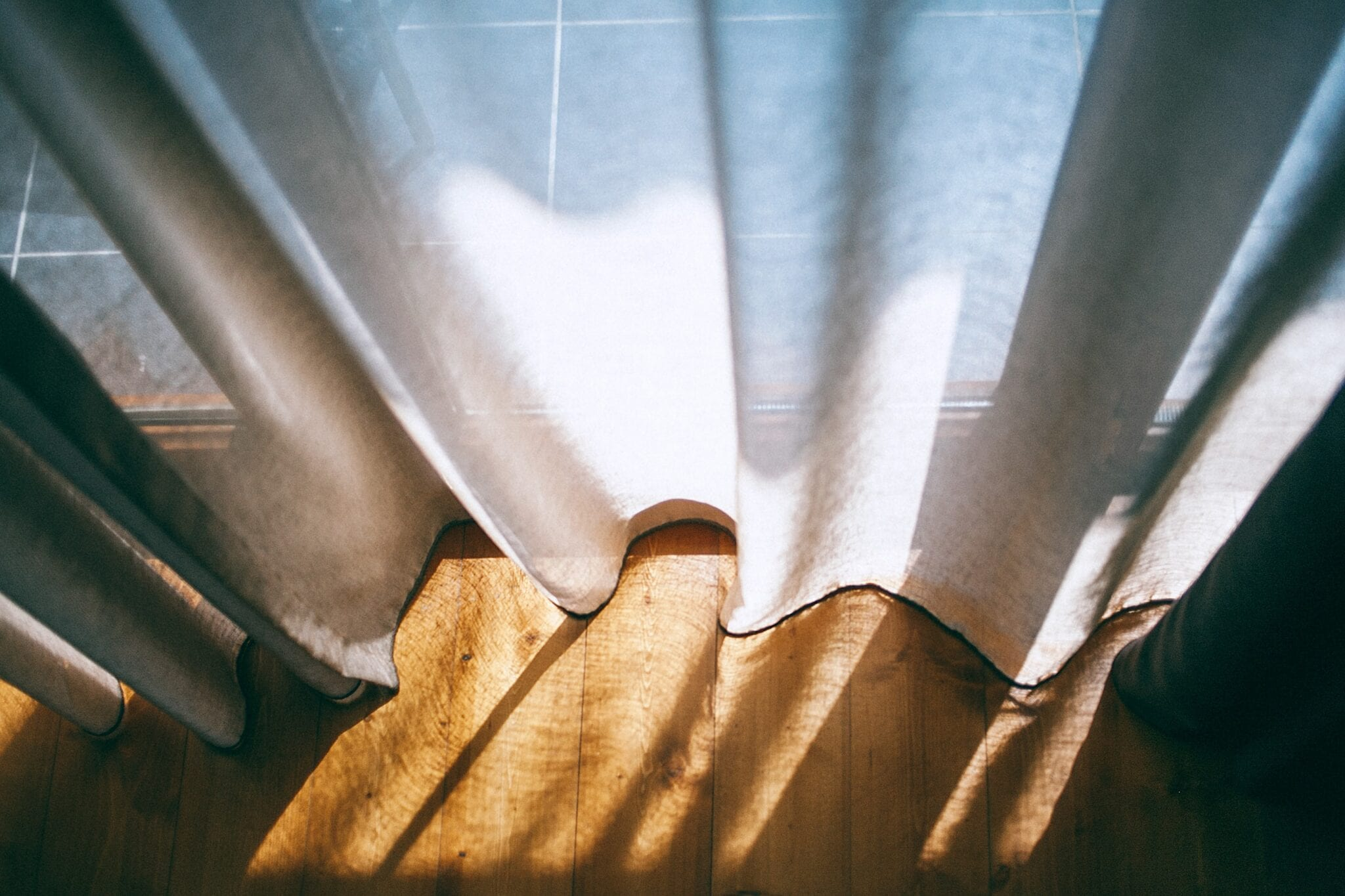 Make Your Conservatory Warmer in Winter: Image of some lightweight beige linen curtains with sunbeams shining through.