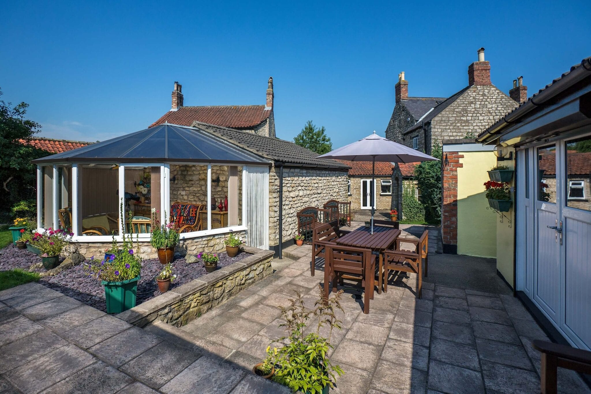 How to Clean a Conservatory Roof: Image of a cottage with a conservatory.
